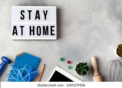 light box with words stay at home, activities that you can do at home sport, cooking, board games, floriculture, planning, laptop. reduce risk of infection and spreading corona virus. copy space