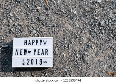 Light box.White label, There is a letter written that Happy New Year 2019.Put on Crushed Gravel.  concept:New Year's Day festival.Used as a background image