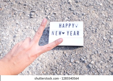 Light box.White label, There is a letter written that Happy New Year .Put on Crushed Gravel.  Hold two fingers. concept:New Year's Day festival.