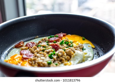 Light breakfast, fried egg with minced pork, Chinese sausage and spring onion on top in the black and red pan. Indochina pan-fried egg with toppings, thai style. Easy cooking at home.