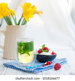 Light breakfast at home, a bouquet of fresh spring flowers in the Kushina. A glass of tea with mint and a bowl of cottage cheese with berries of red raspberries and currants. Yellow daffodils. card.