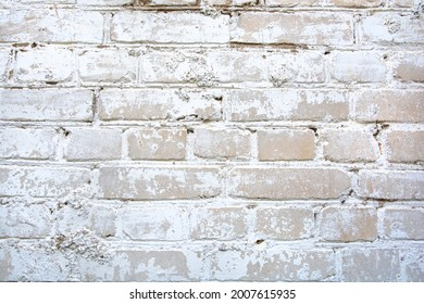 light brick wall with peeling whitewash and cracks