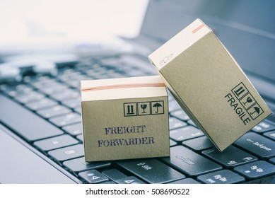 Light brown cardboard boxes on a laptop keyboard. An idea of transportation that can be done easily nowadays using an online internet at hand. Shipping / freight forwarding business concept.