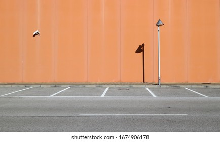 Light brown concrete wall with a lamppost and a surveillance camera. Sidewalk and asphalt road with parking in front. Background for copy space