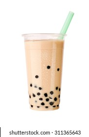 Light brown creamy bubble tea with milk and black tapioca with a green straw in a transparent cup isolated on white