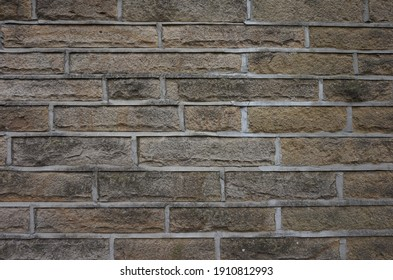 Light brown and grey stone old building wall with light grout. Beautiful old stone pattern background.