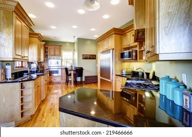 Light brown kitchen cabinets with black shiny counter tops