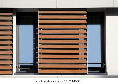 Light brown louvers / blinds over window. Lath structure. Abstract modern architecture background photo. Office or residential building exterior or interior fragment.