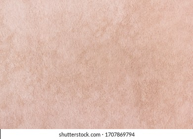 Light brown shaggy fabric for upholstery in macro. Abstract background from a plush fleece surface of soft tissue of light mustard color close-up. Flock fabric.