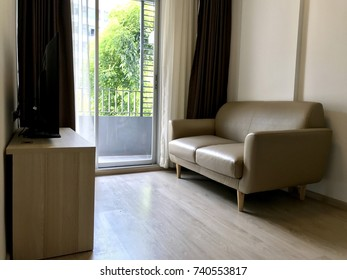 A light brown sofa which placed on the wooden floor is in the living room. The beige couch which made from pvc leather is pasted in the corner of apartment.