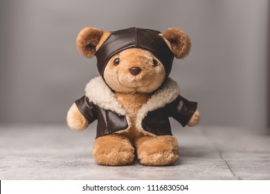 Light brown teddy bear with pilot suit