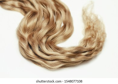 Light brown wavy human hair on white background. Beauty salon. Hair Extensions.