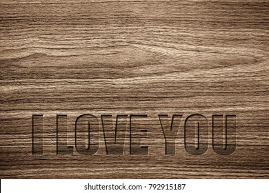 Light brown wood grain texture with a special carving I LOVE YOU message.