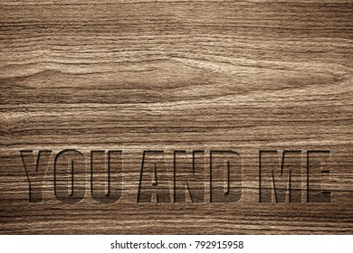 Light brown wood grain texture with a special carving YOU AND ME message.