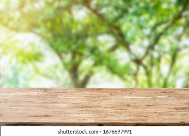 light brown wood table on blurred public garden background with sunlight