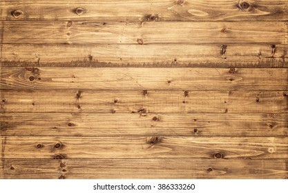Light brown wood texture background viewed from above. The wooden planks are stacked horizontally and have a worn look. This surface would be great as design element for a wall, floor, table etc.