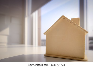 Light brown wooden model home with shadow  Sun light from back side of glass window. Copy space for text. Concept of background, wallpaper,  homesickness, real estate, property. Selective focus.