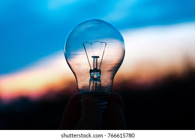 Light Bulb above sunset. Bulb transparent lamp in man's hand. Alternative solar energy in urban, city, town night life. Symbol, concept of business new creative idea. Save eco energy.