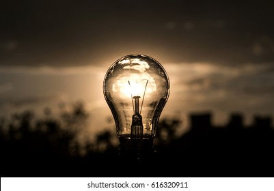Light Bulb above sunset urban houses. bulb transparent lamp in man's alternative solar energy in urban, city, town night life. Symbol, concept of business new creative idea. Save eco energy.