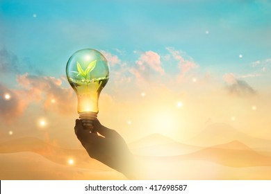 Light bulb against nature on desert mountain background. Ecological and energy concept