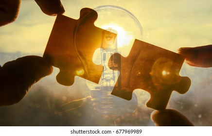 Light Bulb between two piece of puzzle . bulb lamp alternative solar energy in urban, city, town night life. Symbol, concept of business new creative idea. Save eco energy. wooden jigsaw