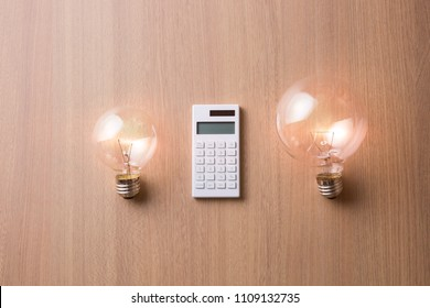 Light bulb and calculator on wooden table