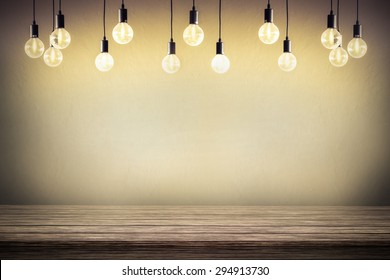 Light bulb with cement wall background,wood table
