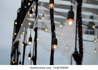Light bulb decor in outdoor wedding party. Abstract blur lamp decoration at night with bokeh effect in background. Selective focus.