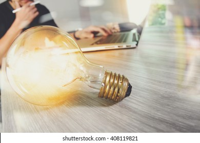 light bulb with designer hand working with laptop computer and creative business strategy as concept