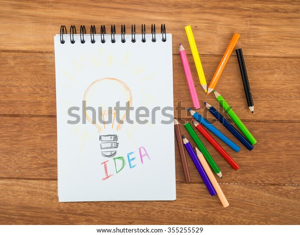 Light bulb drawing with color pencils on wooden table.
