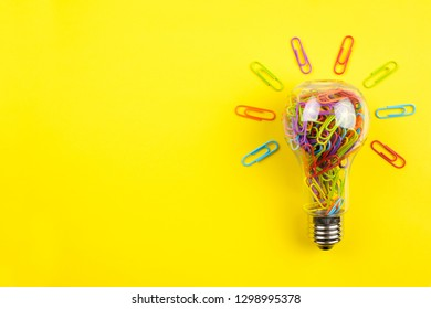 Light bulb filled with multicolor paper clips isolated on yellow background