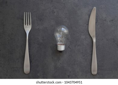 Light bulb, fork and knife on the grey concrete background. Electricity consumption, intellectual property concept. Top view, flat lay, copy space