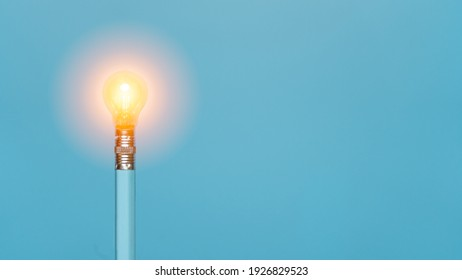 Light bulb glowing on the tip of light blue pencil on light blue background. Creativity, inspiration, idea, motivation, and innovation concept.