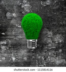 Light bulb with green grass on dark dirty concrete wall background, ECO green energy concept.