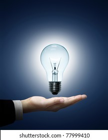 Light bulb in hand businessman on blue background.