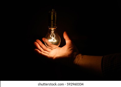 Light bulb and hand, concept of wisdom.
