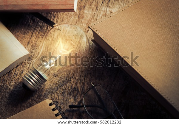 Light bulb lighting in dark tone with book, glasses and pencil, creative idea concept