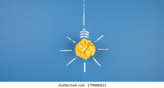 light bulb made of crumpled-up yellow paper on blue background, idea and innovation concept