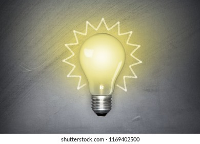 Light bulb on black blackboard background