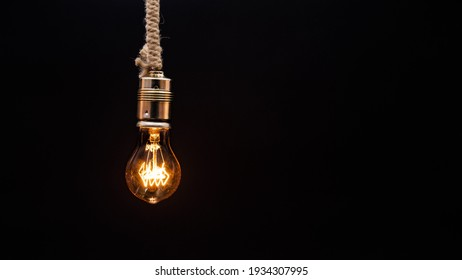 light bulb on dark background old bulb latest technology science electricity yellow light bulb shiny equipment Edison invention reflecting filament transparent old bulb background holder power