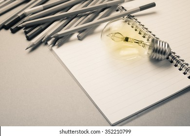 Light bulb on notebook with many pencils as idea for writing concept