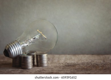 Light bulb on pile of coins in dark vintage tone, creativity idea for money concept