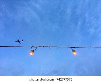 Light bulb on string and airplane with bluesky background