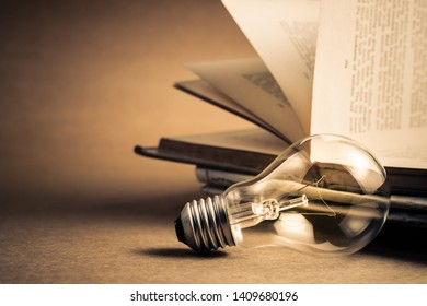 Light bulb with opened old book for reading or knowledge concept