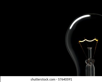 A light bulb over a black background. Tungsten glowing filament. Copy space.