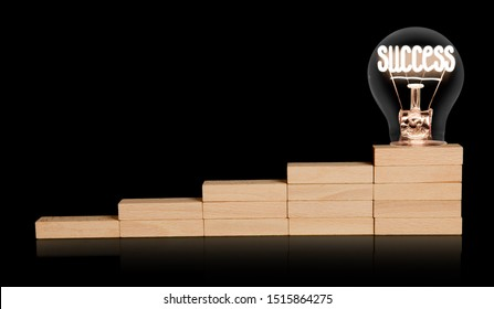 Light bulb with shining fiber in a shape of Success concept word on wooden block ladder isolated on black background.