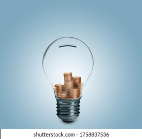 Light bulb with stacked coins inside on light blue background. Energy efficiency, loan, property or business idea concepts