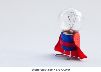 Light bulb super hero dressed in blue suit and red cape. Success man creative concept, fun, kind character. copy space, soft gray background