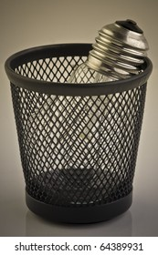Light bulb in trash bin. Metaphor, rejected idea. Sepia.