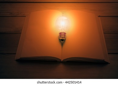 light bulb and vintage book on wood table
